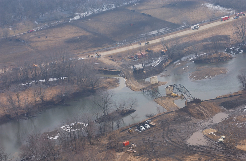 "Photo Credit: Iowa Army National Guard<br /> <br /> The new bridge site in Wapsipinicon State Park during the move.<br /> <br /> The Hale Bridge has helped travelers cross the Wapsipinicon River in Iowa since 1879.  Damaged by floods in 1993, the bridge was closed to traffic in 1997.  However, the bridge was nominated for the National Register of Historic Places in 1998 as the longest-standing bowstring arch bridge in Iowa.  In 2003, the bridge was moved to storage by a planning group composed of representatives from the state DOT, the Federal Highway Administration, Jones County, the Hale area, and the state historical society.  After a three-year restoration, the bridge was relocated 12 miles by air thanks to the Iowa Army National Guard, to Wapsipinicon State Park, where it serves as a pedestrian bridge.<br /> <br /> The move and the restoration were paid for in part with a Transportation Enhancements grant of $159,000.  The move was featured on the History Channel's ""Mega Movers,"" a clip of which can be viewed here: <a href=""http://www.history.com/video.do?name=science&bcpid=1681694253&bclid=1685978756&bctid=1551056441"">http://www.history.com/video.do?name=science&bcpid=1681694253&bclid=1685978756&bctid=1551056441</a>"