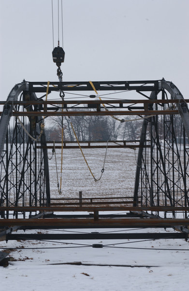 "Photo Credit: Iowa Army National Guard<br /> <br /> The bridge was relocated to its present site on March 8, 2006.<br /> <br /> The Hale Bridge has helped travelers cross the Wapsipinicon River in Iowa since 1879.  Damaged by floods in 1993, the bridge was closed to traffic in 1997.  However, the bridge was nominated for the National Register of Historic Places in 1998 as the longest-standing bowstring arch bridge in Iowa.  In 2003, the bridge was moved to storage by a planning group composed of representatives from the state DOT, the Federal Highway Administration, Jones County, the Hale area, and the state historical society.  After a three-year restoration, the bridge was relocated 12 miles by air thanks to the Iowa Army National Guard, to Wapsipinicon State Park, where it serves as a pedestrian bridge.<br /> <br /> The move and the restoration were paid for in part with a Transportation Enhancements grant of $159,000.  The move was featured on the History Channel's ""Mega Movers,"" a clip of which can be viewed here: <a href=""http://www.history.com/video.do?name=science&bcpid=1681694253&bclid=1685978756&bctid=1551056441"">http://www.history.com/video.do?name=science&bcpid=1681694253&bclid=1685978756&bctid=1551056441</a>"