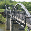 "Photo credit: Russ Coyle<br /> <br /> The Hale Bridge in its present setting.<br /> <br /> The Hale Bridge has helped travelers cross the Wapsipinicon River in Iowa since 1879.  Damaged by floods in 1993, the bridge was closed to traffic in 1997.  However, the bridge was nominated for the National Register of Historic Places in 1998 as the longest-standing bowstring arch bridge in Iowa.  In 2003, the bridge was moved to storage by a planning group composed of representatives from the state DOT, the Federal Highway Administration, Jones County, the Hale area, and the state historical society.  After a three-year restoration, the bridge was relocated 12 miles by air thanks to the Iowa Army National Guard, to Wapsipinicon State Park, where it serves as a pedestrian bridge.<br /> <br /> The move and the restoration were paid for in part with a Transportation Enhancements grant of $159,000.  The move was featured on the History Channel's ""Mega Movers,"" a clip of which can be viewed here: <a href=""http://www.history.com/video.do?name=science&bcpid=1681694253&bclid=1685978756&bctid=1551056441"">http://www.history.com/video.do?name=science&bcpid=1681694253&bclid=1685978756&bctid=1551056441</a>"