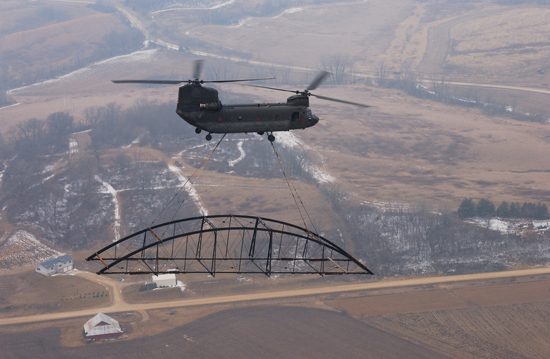 """Photo Credit: Iowa Army National Guard<br /> <br /> A Chinook in flight with one of the bridge spans.<br /> <br /> The Hale Bridge has helped travelers cross the Wapsipinicon River in Iowa since 1879.  Damaged by floods in 1993, the bridge was closed to traffic in 1997.  However, the bridge was nominated for the National Register of Historic Places in 1998 as the longest-standing bowstring arch bridge in Iowa.  In 2003, the bridge was moved to storage by a planning group composed of representatives from the state DOT, the Federal Highway Administration, Jones County, the Hale area, and the state historical society.  After a three-year restoration, the bridge was relocated 12 miles by air thanks to the Iowa Army National Guard, to Wapsipinicon State Park, where it serves as a pedestrian bridge.<br /> <br /> The move and the restoration were paid for in part with a Transportation Enhancements grant of $159,000.  The move was featured on the History Channel's """"Mega Movers,"""" a clip of which can be viewed here: <a href=""""http://www.history.com/video.do?name=science&bcpid=1681694253&bclid=1685978756&bctid=1551056441"""">http://www.history.com/video.do?name=science&bcpid=1681694253&bclid=1685978756&bctid=1551056441</a>"""