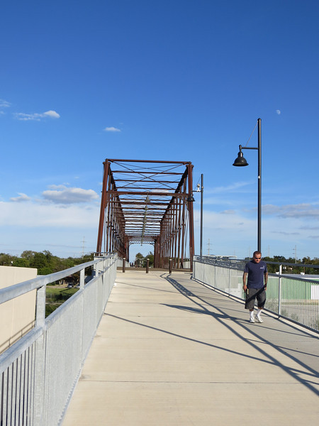 The Hays Street Bridge was originally built by the Southern Pacific railroad to help carriages cross over two railroad tracks on Hays Street. It consists of two iron truss spans, a 225 foot Phoenix Whipple span and a 130 foot Pratt span, which were relocated by the then Galveston, Harrisburg & San Antonio Railway Co. from other parts of their rail lines. The bridges were originally designed by the Phoenix Bridge Company and were relocated to their current position around 1910.<br /> <br /> After years of use, the bridge fell into disrepair and was eventually deemed structurally deficient in the 1980's. Later, in the 1990's several calls to replace the bridge were met by opposition from local residents. Douglas Steadman, the president of the W.E. Simpson Company brought attention to the historical significance of the trusses and helped to get the bridge designated as a Civil Engineering Landmark.<br /> <br /> The efforts of Douglas Steadman and other local activists lead to a Transportation Enhancement award of $2.88 million and a local match of $720,000. With these funds work began to rehabilitate the popular bridge in 2010. The work included rebuilding the two elevated concrete approaches, structurally rehabilitating and painting the truss spans, adding lighting, landscaping, and the addition of interpretive signs. The bridge reopened in August of 2011.
