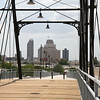 Photo Credit: Markus Haas <br /> <br /> The Hays Street Bridge was originally built by the Southern Pacific railroad to help carriages cross over two railroad tracks on Hays Street. It consists of two iron truss spans, a 225 foot Phoenix Whipple span and a 130 foot Pratt span, which were relocated by the then Galveston, Harrisburg & San Antonio Railway Co. from other parts of their rail lines. The bridges were originally designed by the Phoenix Bridge Company and were relocated to their current position around 1910.<br /> <br /> After years of use, the bridge fell into disrepair and was eventually deemed structurally deficient in the 1980's. Later, in the 1990's several calls to replace the bridge were met by opposition from local residents. Douglas Steadman, the president of the W.E. Simpson Company brought attention to the historical significance of the trusses and helped to get the bridge designated as a Civil Engineering Landmark.<br /> <br /> The efforts of Douglas Steadman and other local activists lead to a Transportation Enhancement award of $2.88 million and a local match of $720,000. With these funds work began to rehabilitate the popular bridge in 2010. The work included rebuilding the two elevated concrete approaches, structurally rehabilitating and painting the truss spans, adding lighting, landscaping, and the addition of interpretive signs. The bridge reopened in August of 2011.