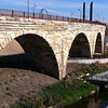 "Over $2 million in TE funds have been used to restore the <a href=""http://www.mrdbridges.com/stoneArch.php"">Stone Arch Bridge</a>, a former railroad bridge crossing the only waterfall, Saint Anthony Falls, on the Mississippi River.  The nationally registered historic bridge dates back to 1883 and is now used by pedestrians, bicyclists, and a short-line trolley.  The Stone Arch Bridge is used daily by commuters and recreation seekers in Minneapolis, nearby suburbs, and the University of Minnesota.  The bridge provides access to <a href=""http://www.minneapolisparks.org/default.asp?PageID=4&parkid=413"">Mill Ruins Park</a> (which received $775,000 in TE funds in 2003 for a pedestrian circulation system) and the St. Anthony Falls Heritage Trail, a two mile trail with an extensive array of interpretive and directional signs noting the early days of the city and the historic flour mill district.  It is also one of many sites along the <a href=""http://www.minneapolisparks.org/grandrounds/home.htm"">Grand Rounds National Scenic Byway</a> (where bicycle and pedestrian wayfinding improvements were implemented through $715,000 in TE funds in 2003).  The restoration of the Stone Arch Bridge would not have been possible had it not been for the partnership between the Minnesota Department of Transportation, the Minnesota Historical Society and the local Saint Anthony Falls Heritage Board."