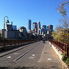 "<b>An iconic view of downtown Minneapolis' skyline from the Stone Arch Bridge.</b>  Over $2 million in TE funds have been used to restore the <a href=""http://www.mrdbridges.com/stoneArch.php"">Stone Arch Bridge</a>, a former railroad bridge crossing the only waterfall, Saint Anthony Falls, on the Mississippi River.  The nationally registered historic bridge dates back to 1883 and is now used by pedestrians, bicyclists, and a short-line trolley.  The Stone Arch Bridge is used daily by commuters and recreation seekers in Minneapolis, nearby suburbs, and the University of Minnesota.  The bridge provides access to <a href=""http://www.minneapolisparks.org/default.asp?PageID=4&parkid=413"">Mill Ruins Park</a> (which received $775,000 in TE funds in 2003 for a pedestrian circulation system) and the St. Anthony Falls Heritage Trail, a two mile trail with an extensive array of interpretive and directional signs noting the early days of the city and the historic flour mill district.  It is also one of many sites along the <a href=""http://www.minneapolisparks.org/grandrounds/home.htm"">Grand Rounds National Scenic Byway</a> (where bicycle and pedestrian wayfinding improvements were implemented through $715,000 in TE funds in 2003).  The restoration of the Stone Arch Bridge would not have been possible had it not been for the partnership between the Minnesota Department of Transportation, the Minnesota Historical Society and the local Saint Anthony Falls Heritage Board."