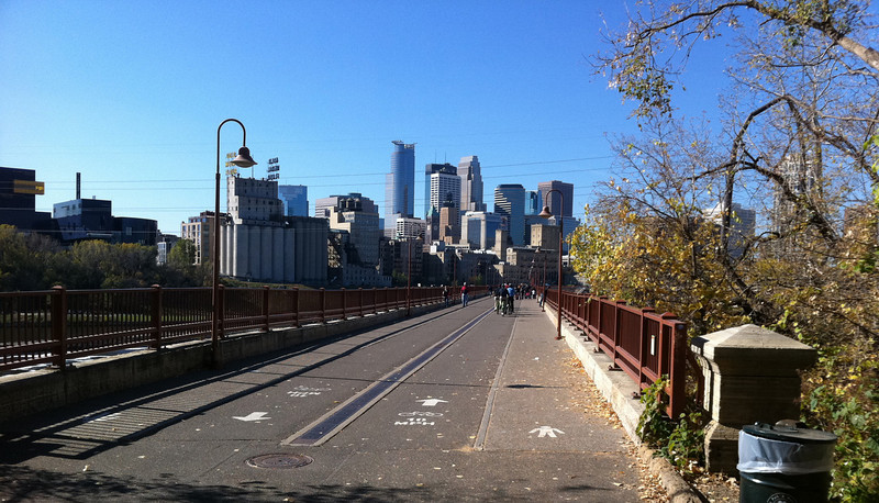 """<b>An iconic view of downtown Minneapolis' skyline from the Stone Arch Bridge.</b>  Over $2 million in TE funds have been used to restore the <a href=""""http://www.mrdbridges.com/stoneArch.php"""">Stone Arch Bridge</a>, a former railroad bridge crossing the only waterfall, Saint Anthony Falls, on the Mississippi River.  The nationally registered historic bridge dates back to 1883 and is now used by pedestrians, bicyclists, and a short-line trolley.  The Stone Arch Bridge is used daily by commuters and recreation seekers in Minneapolis, nearby suburbs, and the University of Minnesota.  The bridge provides access to <a href=""""http://www.minneapolisparks.org/default.asp?PageID=4&parkid=413"""">Mill Ruins Park</a> (which received $775,000 in TE funds in 2003 for a pedestrian circulation system) and the St. Anthony Falls Heritage Trail, a two mile trail with an extensive array of interpretive and directional signs noting the early days of the city and the historic flour mill district.  It is also one of many sites along the <a href=""""http://www.minneapolisparks.org/grandrounds/home.htm"""">Grand Rounds National Scenic Byway</a> (where bicycle and pedestrian wayfinding improvements were implemented through $715,000 in TE funds in 2003).  The restoration of the Stone Arch Bridge would not have been possible had it not been for the partnership between the Minnesota Department of Transportation, the Minnesota Historical Society and the local Saint Anthony Falls Heritage Board."""