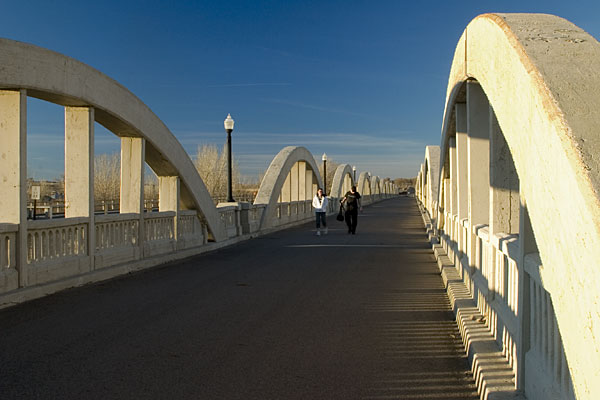 """<a href=""""http://www.flickr.com/people/photokayaker/"""">Photo Credit</a> The Rainbow Arch Bridge in Fort Morgan, Colorado, is the only bridge of its kind in the state and one of the longest of its kind in the country. The remarkable bridge design includes 11 graceful arches that together stretch 1,100 feet over the South Platte River. This exceptional design won the bridge a space on the National Register of Historic Places and designation as a Colorado Civil Engineering Landmark. The unique character of the bridge also inspired a local community group, the Fort Morgan Historical Society, to save the aging bridge from collapse in the early 1990s. The Society worked with the city of Fort Morgan and the Colorado Historical Society to generate matching funds for a two- phase TE award to restore the bridge for pedestrian use. Today, it is a popular tourist attraction and a center for community events such as the annual Tin Man Triathlon. In addition, the Rainbow Arch Bridge serves as the entrance to the <a href=""""http://www.coloradodot.info/travel/scenic-byways/northeast/pawnee-pioneer-trails"""">Pawnee  Pioneer Trails</a>, a part of Colorado's Scenic and Historic Byways system."""