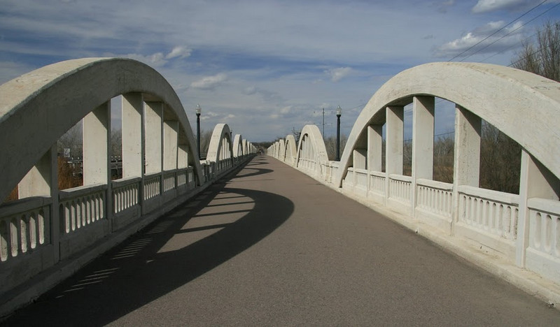 """<a href=""""https://www.google.com/profiles/timshel40"""">Photo Credit</a> The Rainbow Arch Bridge in Fort Morgan, Colorado, is the only bridge of its kind in the state and one of the longest of its kind in the country. The remarkable bridge design includes 11 graceful arches that together stretch 1,100 feet over the South Platte River. This exceptional design won the bridge a space on the National Register of Historic Places and designation as a Colorado Civil Engineering Landmark. The unique character of the bridge also inspired a local community group, the Fort Morgan Historical Society, to save the aging bridge from collapse in the early 1990s. The Society worked with the city of Fort Morgan and the Colorado Historical Society to generate matching funds for a two- phase TE award to restore the bridge for pedestrian use. Today, it is a popular tourist attraction and a center for community events such as the annual Tin Man Triathlon. In addition, the Rainbow Arch Bridge serves as the entrance to the <a href=""""http://www.coloradodot.info/travel/scenic-byways/northeast/pawnee-pioneer-trails"""">Pawnee  Pioneer Trails</a>, a part of Colorado's Scenic and Historic Byways system."""
