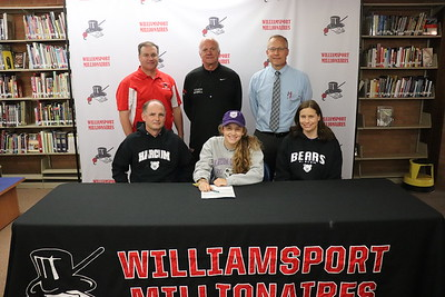 Sydney Bruno signs to play soccer at Harcum College.  From back left: Athletic Director Sean McCann, Head Soccer Coach Scott McNeil and Head Principal Dr. Brandon Pardoe. Seated with Bruno, center, are her parents Chris and Vince.