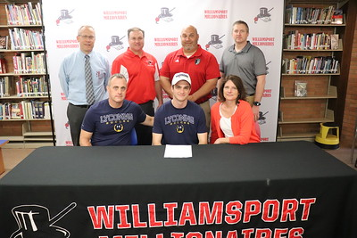 JR Confair signs to play soccer at Lycoming College.  From back left: Head Principal Dr. Brandon Pardoe, Athletic Director Sean McCann, and soccer coaches Lee Carr and Phillip Marrie. Seated with Confair, center, are his parents Dave and Brette Confair.