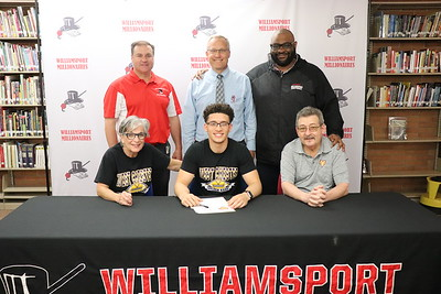 Marcus Simmons signs to play football at West Chester University.  From back left: Athletic Director Sean McCann, Head Principal Dr. Brandon Pardoe, Head Football Coach Chuck Crews. Seated with Simmons, his grandparents Sharon and Frank Scarfo.