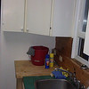 Before: Kitchen, corner cabinet SW corner. Below it is freestanding butcher block table.