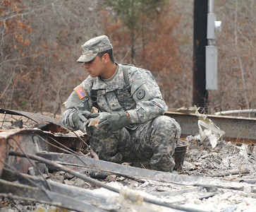 Pfc.  Jonathan Fillmore of the 436th Chemical Detachment assists with the cleanup of debris from the wildfires Nov. 19 in Bastrop, Texas.