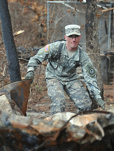 Pfc. Joshua Doucet of the 436th Chemical Detachment assists with the cleanup of debris from the wildfires Nov. 19 in Bastrop, Texas.
