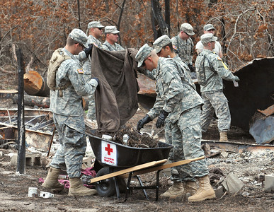 Cadet Roy Gann, Cadet Noah Koubenec and Pfc. Jonathan Fillmore of the 436th Chemical Detachment assist with the cleanup of debris from the wildfires Nov. 19 in Bastrop, Texas.