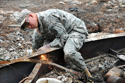 Staff Sgt. Jereme Walker of the 436th Chemical Detachment assists with the cleanup of debris from the wildfires Nov. 19 in Bastrop, Texas.