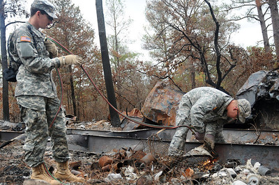 Pfc.  Jacob Putalavage and Staff Sgt.  Jereme Walker of 436th Chemical Detachment use a cutting torch to remove the remains of a mobile home from the wildfires Nov. 19 in Bastrop, Texas.