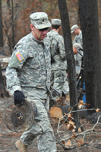 Spc. Michael Gass of the 436th Chemical Detachment assists with the cleanup of debris from the wildfires Nov. 19 in Bastrop, Texas.
