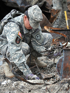 Staff Sgt. Nikki Shearman of the 436th Chemical Detachment assists with the cleanup of debris from the wildfires Nov. 19 in Bastrop, Texas.