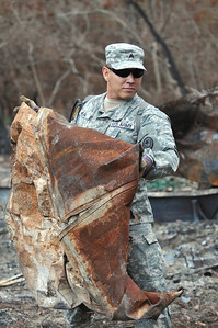 Sgt. Abran Mejia of the 436th Chemical Detachment assists with the cleanup of debris from the wildfires Nov. 19 in Bastrop, Texas.