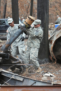 SPC Edwin Hines and SPC Jose Jusino of the 436th Chemical Detachment assist with the cleanup of debris from the wildfires Nov. 19 in Bastrop.