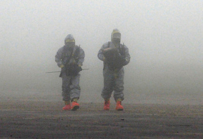 The 436th Chemical Company walk though the fog early in the morning to setup hazardous material detectors for the 6th CERFP EAVAL.