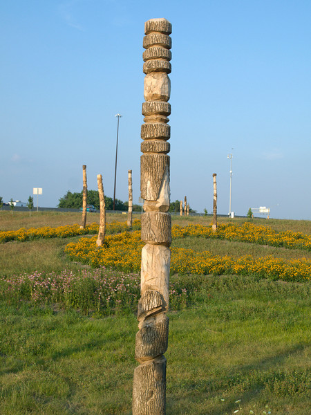 """Totem pole art at the Harding Street interchange. A total of 58 poles were designed by Jason Bord and installed.   The 2010 Lilly Global Day of Service focused on the six-mile I-70 corridor running from the airport through downtown Indianapolis. <a href=""""http://www.kibi.org/"""">Keep Indianapolis Beautiful, Inc.</a> (KIBI) a local nonprofit with a 30-year track record of successful beautification partnerships in Indianapolis, envisioned something much grander than the usual highway ramps. Bringing together the city of Indianapolis, the Indiana Department of Transportation, community leaders, neighborhood groups, and the private sector, KIBI coordinated a master planning process for the corridor with the landscape architecture firm <a href=""""http://www.bdmd.com/"""">Browning Day Mullins Deerdorf</a>. The project culminated in the 2010 Eli Lilly Day of Service, where over 8,000 Lilly employees added low maintenance vegetation, planted trees, and positioned totem poles and lotus leaf sculptures, transforming the I-70 corridor. The $1 million TE grant supporting the project was matched by an additional $1 million from Eli Lilly in addition to the volunteer labor, a major private investment on behalf of public infrastructure.  Learn more about this extraordinary project at  http://www.agreenerwelcome.org/."""