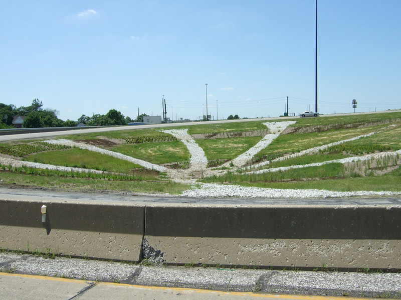"""The future site of public art designed by Biagio Azzarelli at the Meridian Street Interchange.  The 2010 Lilly Global Day of Service focused on the six-mile I-70 corridor running from the airport through downtown Indianapolis. <a href=""""http://www.kibi.org/"""">Keep Indianapolis Beautiful, Inc.</a> (KIBI) a local nonprofit with a 30-year track record of successful beautification partnerships in Indianapolis, envisioned something much grander than the usual highway ramps. Bringing together the city of Indianapolis, the Indiana Department of Transportation, community leaders, neighborhood groups, and the private sector, KIBI coordinated a master planning process for the corridor with the landscape architecture firm <a href=""""http://www.bdmd.com/"""">Browning Day Mullins Deerdorf</a>. The project culminated in the 2010 Eli Lilly Day of Service, where over 8,000 Lilly employees added low maintenance vegetation, planted trees, and positioned totem poles and lotus leaf sculptures, transforming the I-70 corridor. The $1 million TE grant supporting the project was matched by an additional $1 million from Eli Lilly in addition to the volunteer labor, a major private investment on behalf of public infrastructure.  Learn more about this extraordinary project at  http://www.agreenerwelcome.org/."""