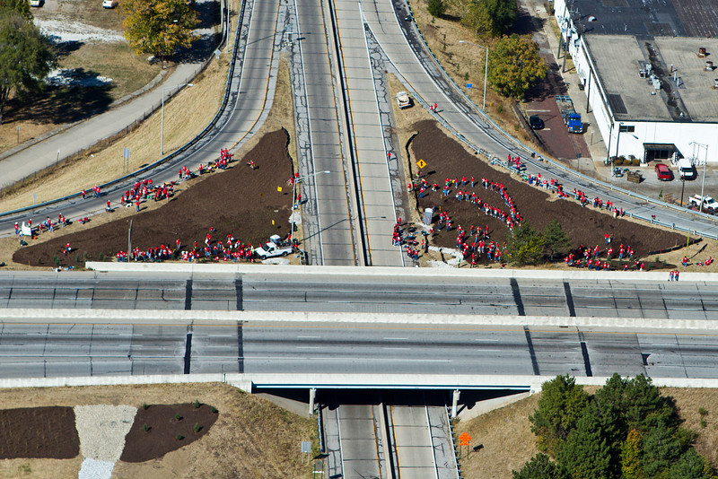 "Overview of volunteers helping to make I-70 more beautiful.   The 2010 Lilly Global Day of Service focused on the six-mile I-70 corridor running from the airport through downtown Indianapolis. <a href=""http://www.kibi.org/"">Keep Indianapolis Beautiful, Inc.</a> (KIBI) a local nonprofit with a 30-year track record of successful beautification partnerships in Indianapolis, envisioned something much grander than the usual highway ramps. Bringing together the city of Indianapolis, the Indiana Department of Transportation, community leaders, neighborhood groups, and the private sector, KIBI coordinated a master planning process for the corridor with the landscape architecture firm <a href=""http://www.bdmd.com/"">Browning Day Mullins Deerdorf</a>. The project culminated in the 2010 Eli Lilly Day of Service, where over 8,000 Lilly employees added low maintenance vegetation, planted trees, and positioned totem poles and lotus leaf sculptures, transforming the I-70 corridor. The $1 million TE grant supporting the project was matched by an additional $1 million from Eli Lilly in addition to the volunteer labor, a major private investment on behalf of public infrastructure.  Learn more about this extraordinary project at  http://www.agreenerwelcome.org/."