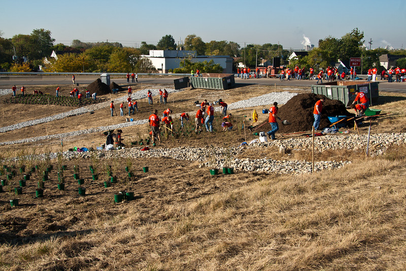 """Volunteers busy planting trees.   The 2010 Lilly Global Day of Service focused on the six-mile I-70 corridor running from the airport through downtown Indianapolis. <a href=""""http://www.kibi.org/"""">Keep Indianapolis Beautiful, Inc.</a> (KIBI) a local nonprofit with a 30-year track record of successful beautification partnerships in Indianapolis, envisioned something much grander than the usual highway ramps. Bringing together the city of Indianapolis, the Indiana Department of Transportation, community leaders, neighborhood groups, and the private sector, KIBI coordinated a master planning process for the corridor with the landscape architecture firm <a href=""""http://www.bdmd.com/"""">Browning Day Mullins Deerdorf</a>. The project culminated in the 2010 Eli Lilly Day of Service, where over 8,000 Lilly employees added low maintenance vegetation, planted trees, and positioned totem poles and lotus leaf sculptures, transforming the I-70 corridor. The $1 million TE grant supporting the project was matched by an additional $1 million from Eli Lilly in addition to the volunteer labor, a major private investment on behalf of public infrastructure.  Learn more about this extraordinary project at  http://www.agreenerwelcome.org/."""