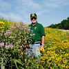 Many of Iowa's 99 counties employ a roadside manager. These individuals are responsible for controlling erosion, weeds, and brush along hundreds of miles of county road. Van Buren County's roadside manager, Wayne Thornsberry, is shown in a TA-funded native planting. <br /> <br /> Iowa's Integrated Roadside Vegetation Management (IRVM) Program Office has been awarded FHWA funding to purchase native prairie seed for use in county rights-of-way since 1998. Approximately 1000 roadside acres have been planted each year. These plantings are well-adapted for use on roadsides, providing weed and erosion control, storm water management, and habitat corridors. The IRVM Program Office is located at the University of Northern Iowa's Tallgrass Prairie Center.