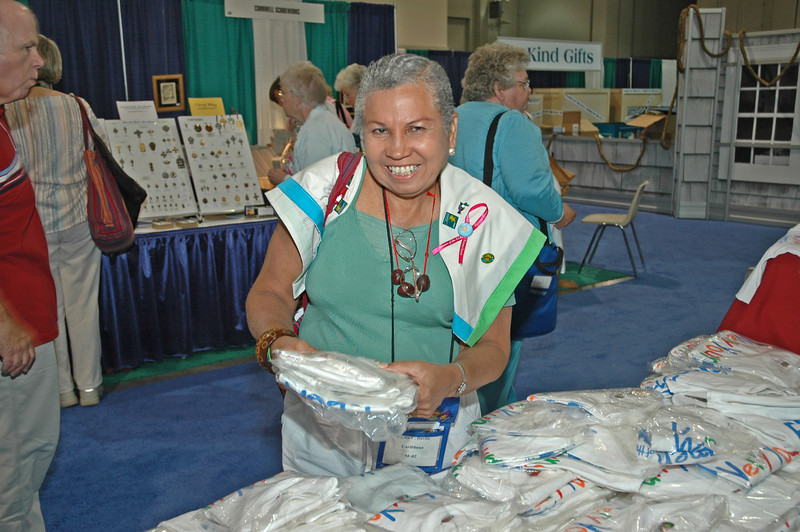 "Lydia Davila finds a bargain in the exhibit hall, ""Gather at the River."""