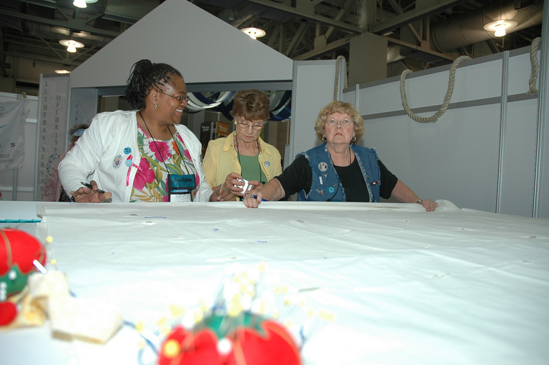 "Annie Allen, Lila Ellison, and Alda Rydin arrange the ""holey cloth."""