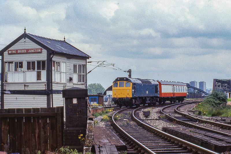 28th May 1981:  At  2.13pm crossing Mitre Bridge Junction is 25303  with an interesting Brake Third Mk 1 coach.  The colours are wrong for Blood and Custarrd and the ends wwere always black on a plain coach ! so !!