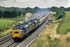 26th Aug 1982:  The sunshine at Hungerford Common had vanished for the day but a pair od 37 s was worth a shot.  At 4.25pm 37268 & 37207 are working the Yeoman hoppers to Merehead from Brentford.  The view has changed for the good and the bad.  The field on the left is a car park with a spikey fence but the ugly shed has gone. openiing up the view.