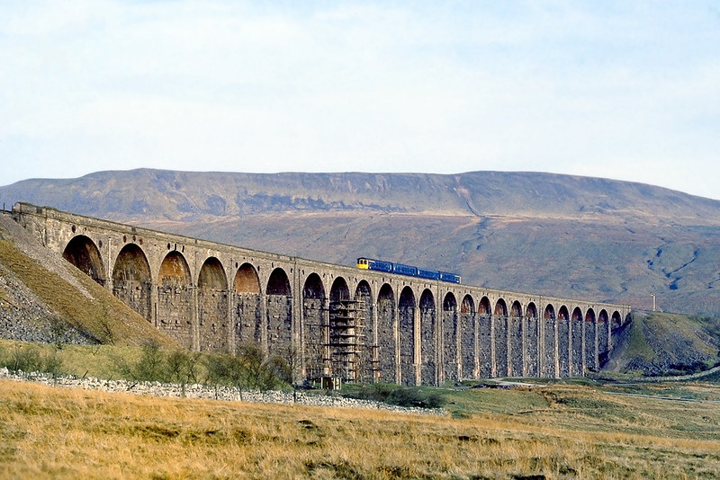 26th Apr 82:    At 07.14 in the morning and with a backdrop of the 2400 ft Whernside  a Class 104 DMU heads south over Ribblehead Viaduct.