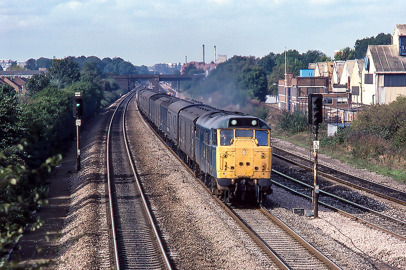 31st Oct-1983:  Hammering  along on the Up Main through Langley is 31306 with the empty news paper vans from the West of England.  The large  Langley Alloys factory on the right had not much longer to live  before it was replaced by office blocks