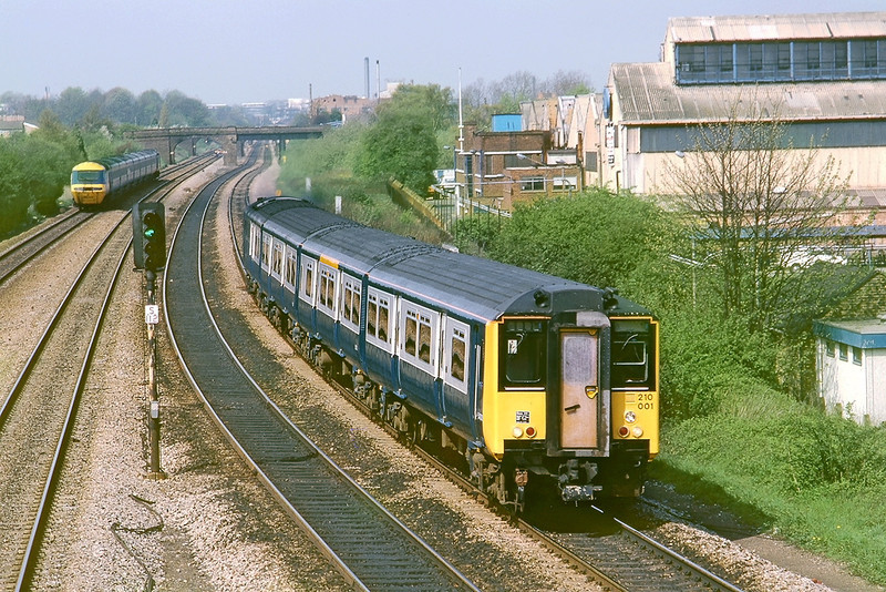 29th Apr 83:  The 09.52 from Reading to Paddington formed of 210001 arrives at Langley.  The old 'Langley Alloys' factory can be seen on the right