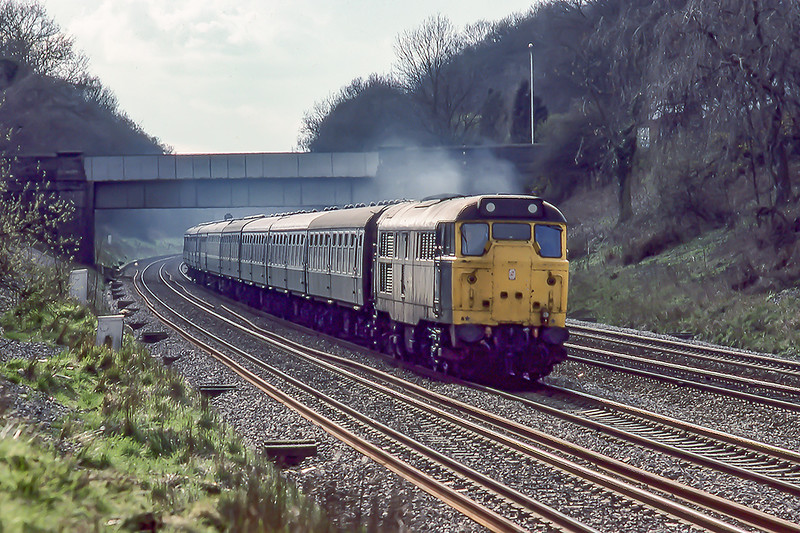 4th April 1983: On a Bank Holiday Special 31424 hammers up the Main through the Sonning Cutting at Woodley