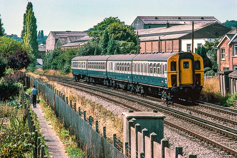 14th Aug 1983: 4VEP  7703 forming the 11.32 from Reading to Waterloois is passing the long departed industrial complex on the edge of Egham.