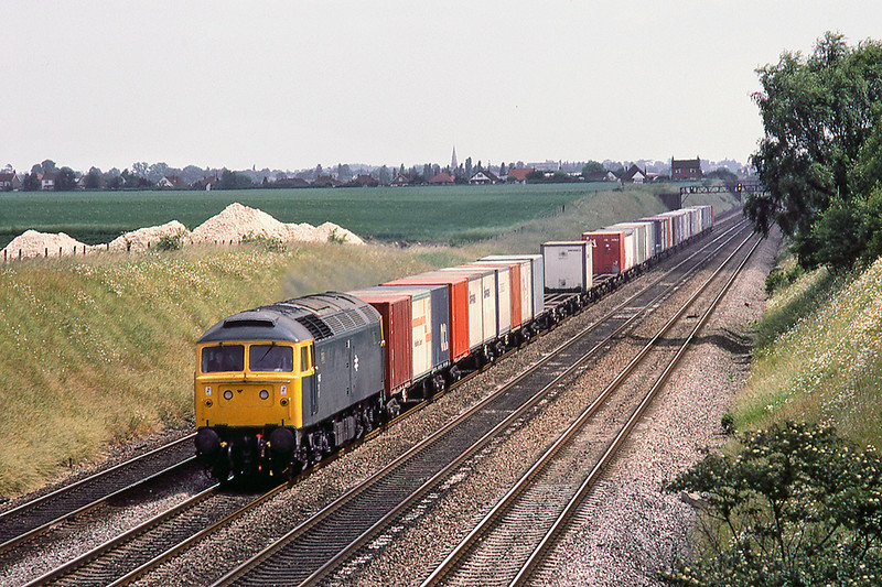 28th Jun 1983:  On the Down Relief at Shottesbrooke ,between Maidenhead and Twyford ,is 47145 with a Freightliner.  The white pyramids were  the temporary result of a pipeline that was being laid I  believe..
