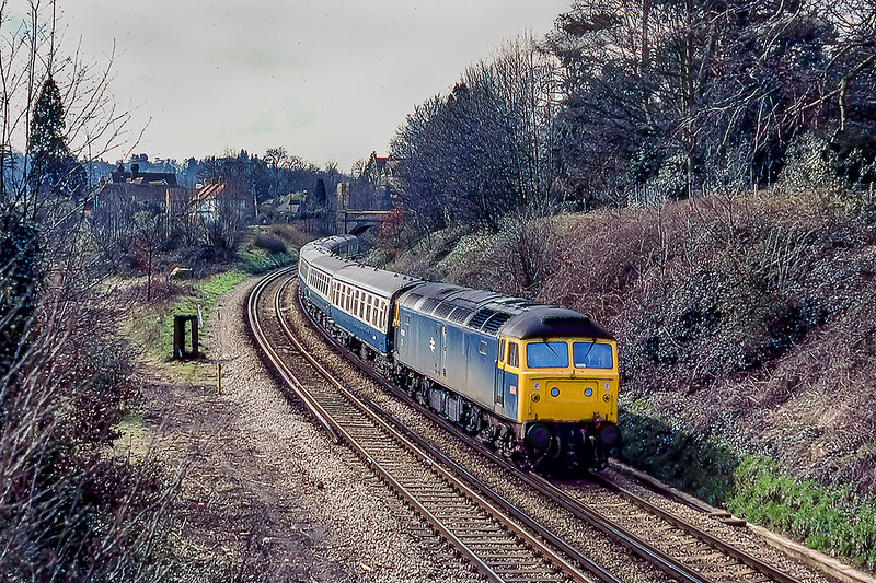 29th March 1983:  The 110.5 from Portsmouth to Manchester with 47563 on the front is about to pass through Farncombe station on the Pompey direct line