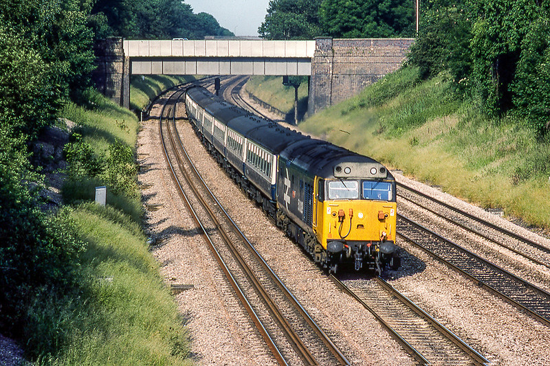 25th Jun  1983:  Pictured from the Duffield Road  bridge in the Sonning Cut6ting is 50049 'Defiance' as it works the 16.25 from Oxford to Paddington.  In the days of semaphore signaling Woodley Signal Box was in the foreground on the left.