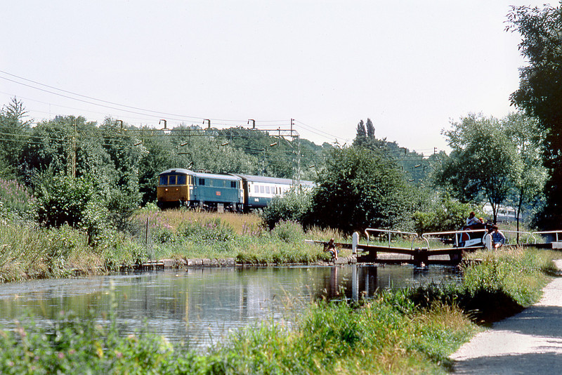 """21st Jul 83:  The 12.00 Euston to Liverpool in the hands of 86256 """"Pebble Mill"""" passes boaters on the Grand Union Canal at Berkamstead"""