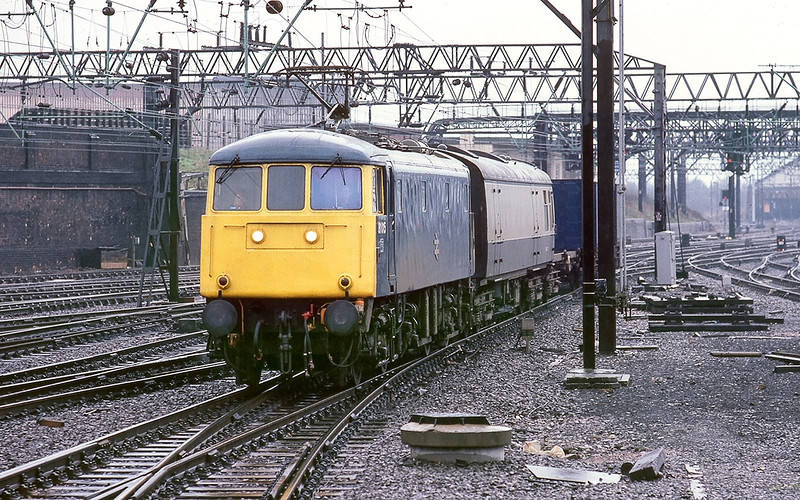 19th Apr 83:  81015 at Crewe on a very wet day with a Bullion train.  Guards and staff in the coach and the Lolly in the container.