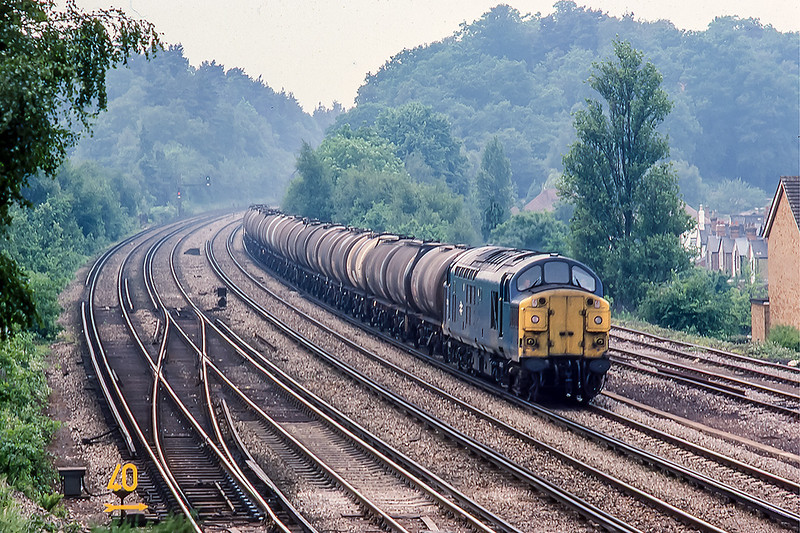 23rd Jun 1983:  37060 is working empty oil tanks to Thames Have from the Mitcheldever storage terminal though Woking
