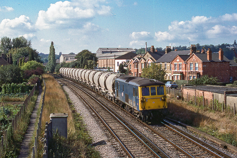 26th Sep 1984:  73118 on the Rugby Cement empties at Egham.  Houses now occupy  both the site of the allotments on the left and factory on the righ.