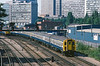 5th Jul 1984:  Judging by all the open windows in the non airconditioned office block at 10.02 it was pretty warm already.  Class 421 (4CIG) 7370 is leaving East roydon with the 09.48 from Three Bridges to Victoria..