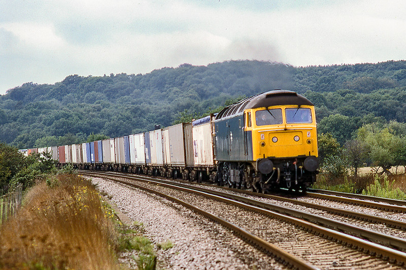 27th Sep 1984: Nearing the Prune Hill level crossing on the out skirts of Egham is 47056 working a Freightliner from Southampton  to East London