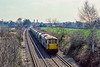 3rd Apr 1984:  The two uprights in the background are the suports of the  railway bridge over the M25 at-Lyne.  72135 is hauling empty Rugby cement tanks towards Virginia Water..