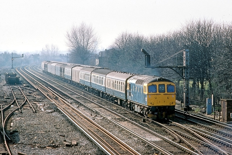 16th Mar 83:  The Eastleigh to Clapham vans behind 33001 nears Wimbledon Station